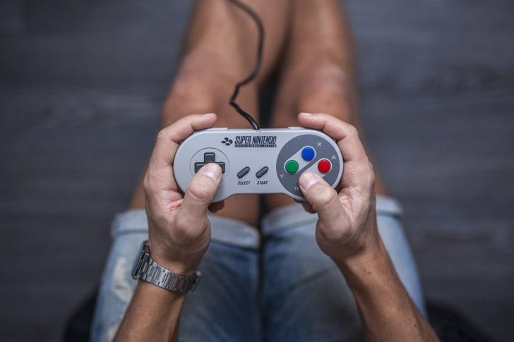 Person holding Super Nintendo controller