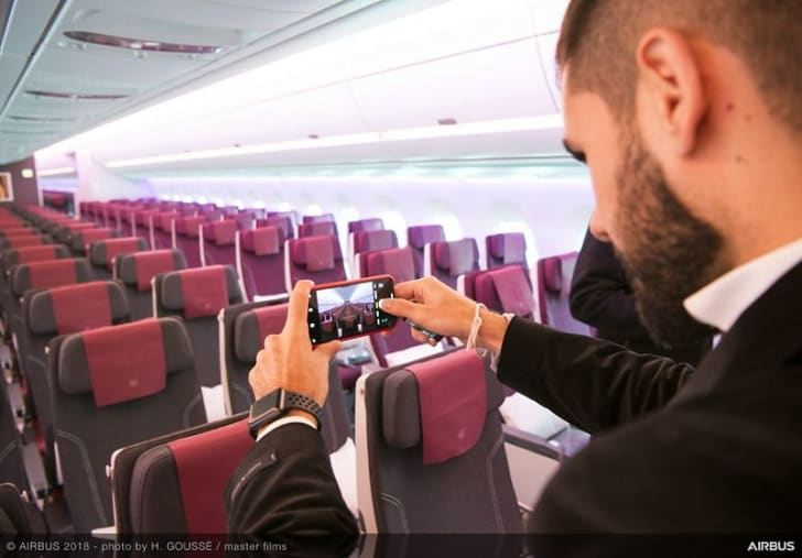 A journalist takes a photo of the A350-1000 cabin