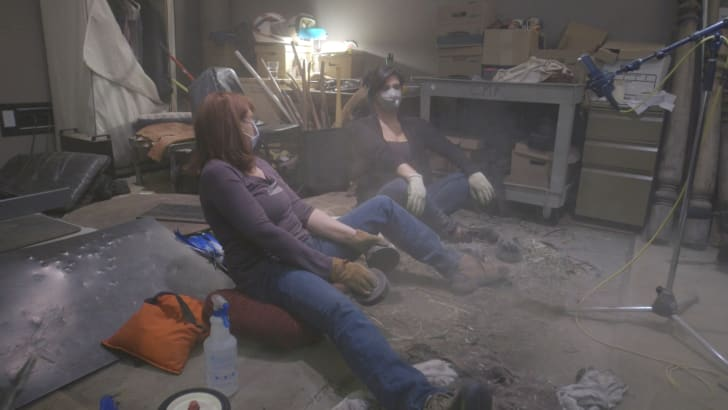 Two women in surgical masks sit on the floor creating fathier sound effects.