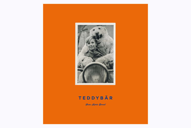 The orange cover of 'Teddybär' shows a person in a polar bear suit with his arms wrapped around a smiling boy.
