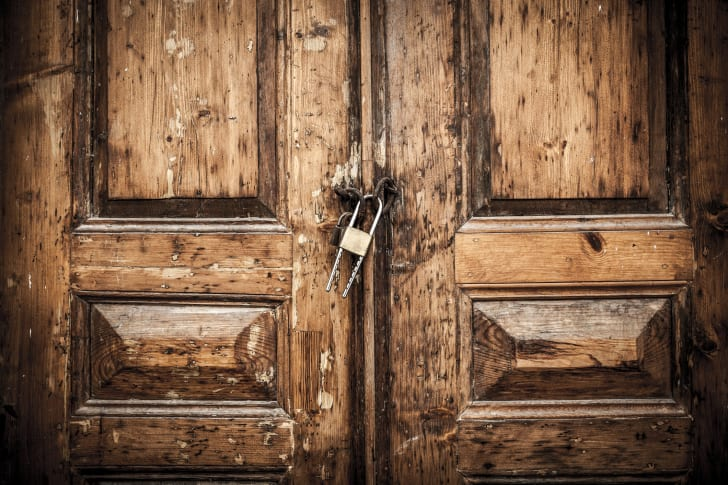 Heavy wooden doors locked in the middle with a padlock.