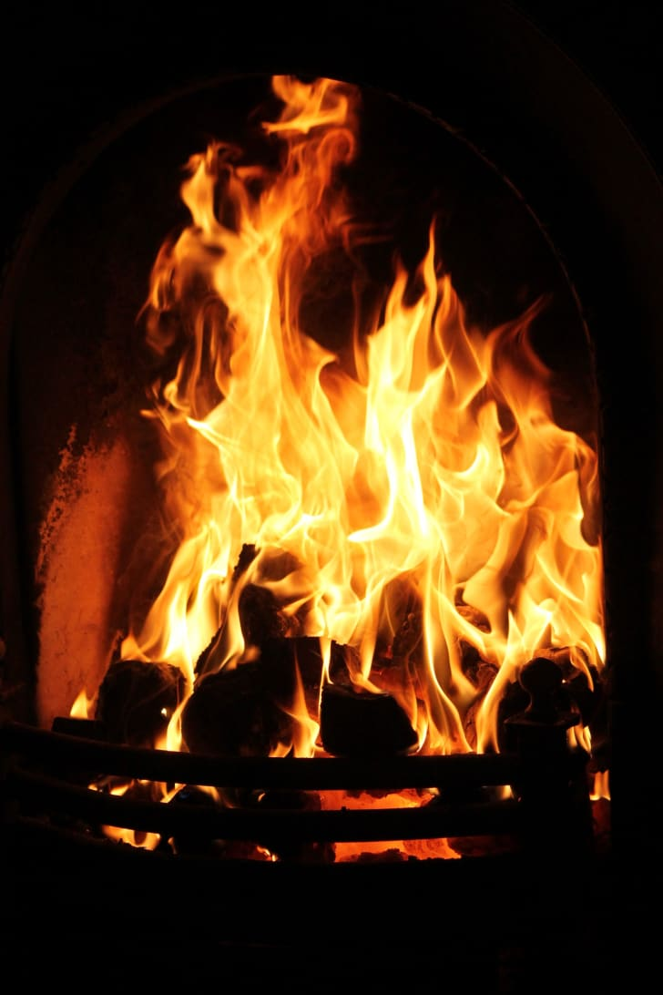 Logs burning in a fireplace with large flames licking off of them.