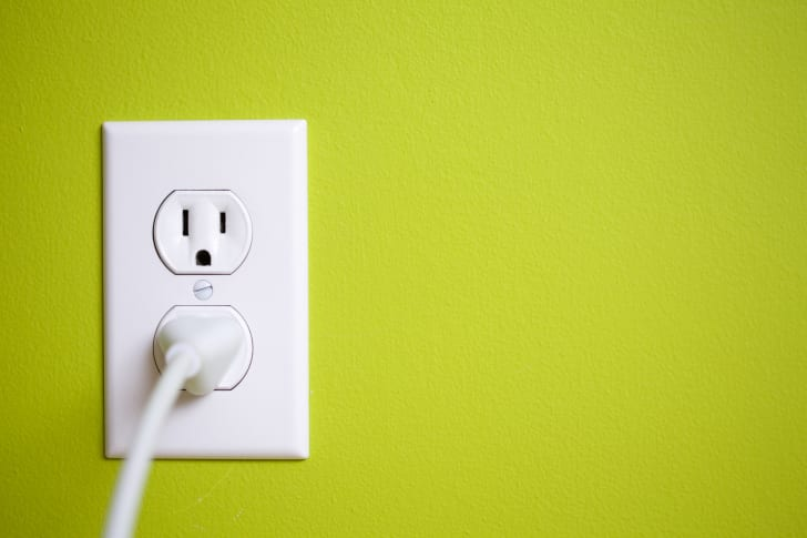 A white outlet with a cord plugged into it on a lime green wall.