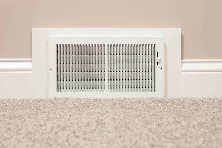 A white HVAC register set into a tan wall with neutral-colored carpet in the foreground.