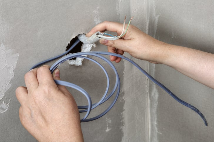 A hand is holding electrical work that has been pulled through a cement wall.