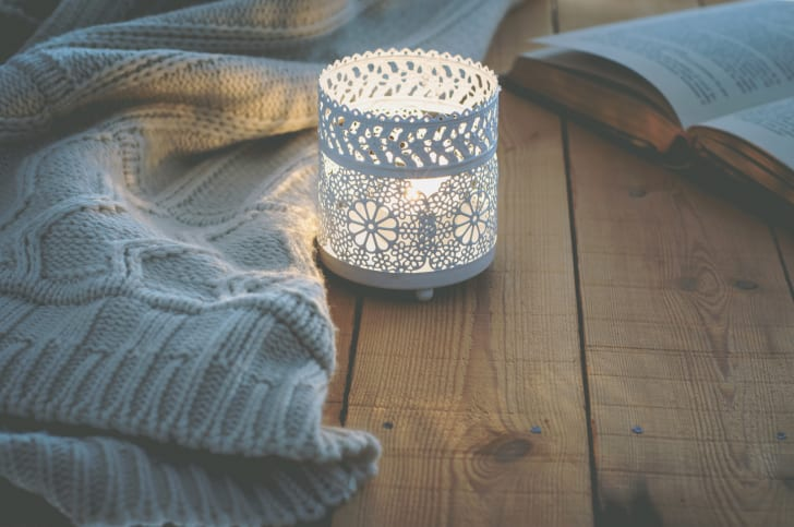 A candle in a white candle holder sitting on top of a rustic wood table. A knit blanket and an open book lie nearby.