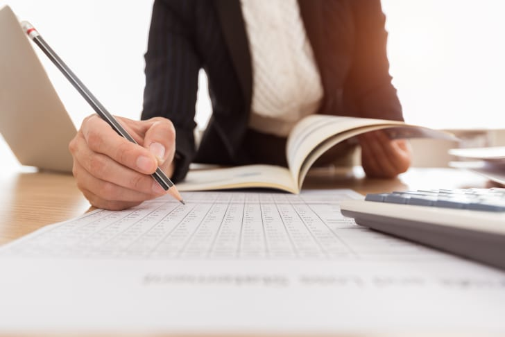 A person holding a pencil over a piece of paper with a book open in the background.