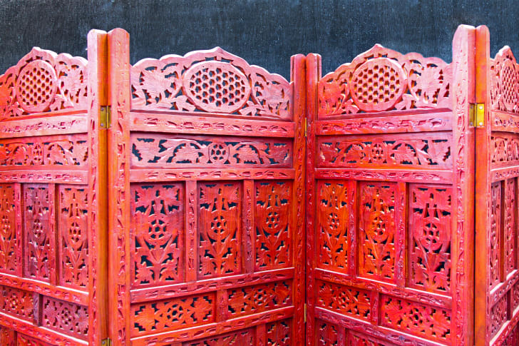 A red, wooden folding screen with intricate cut outs.