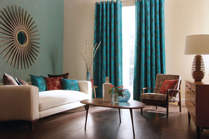 Heavy turquoise drapes adorn the windows in a modern-looking living room with a low white couch and sunburst mirror.