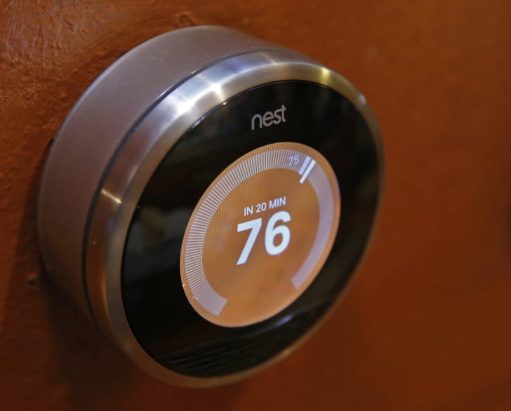 A circular thermostat that's silver on the outside with an electronic screen that shows the number 76 on an orange background.