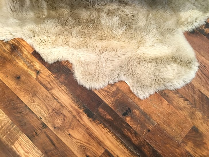 A white sheepskin rug on a rustic wooden floor.