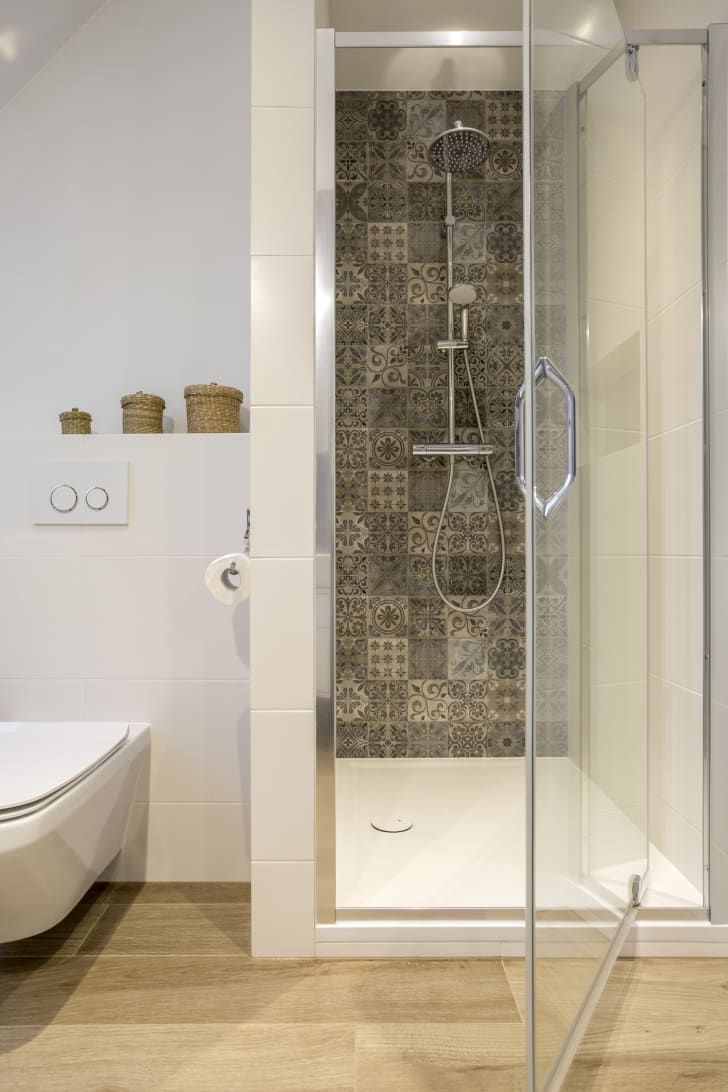 A clear shower door open to show the tiled wall inside. A white bathtub is off to the left.