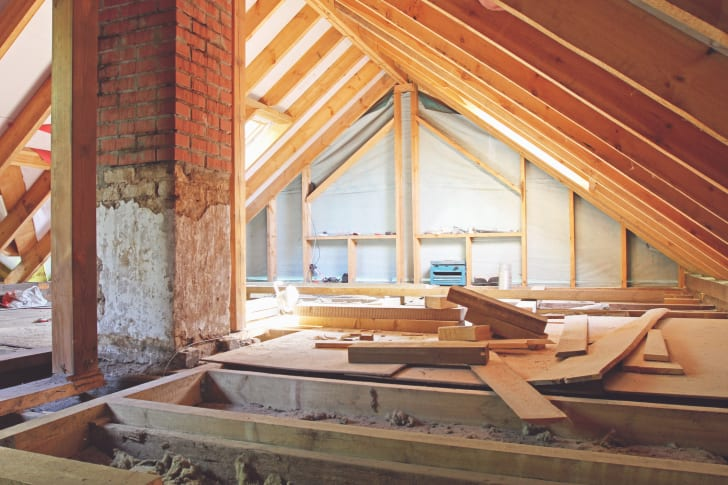 An attic being framed and insulated, with tools splayed out across the floor.