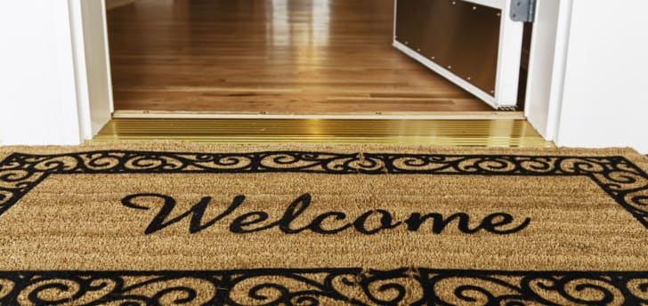 A welcome mat with a gold door threshold behind it.