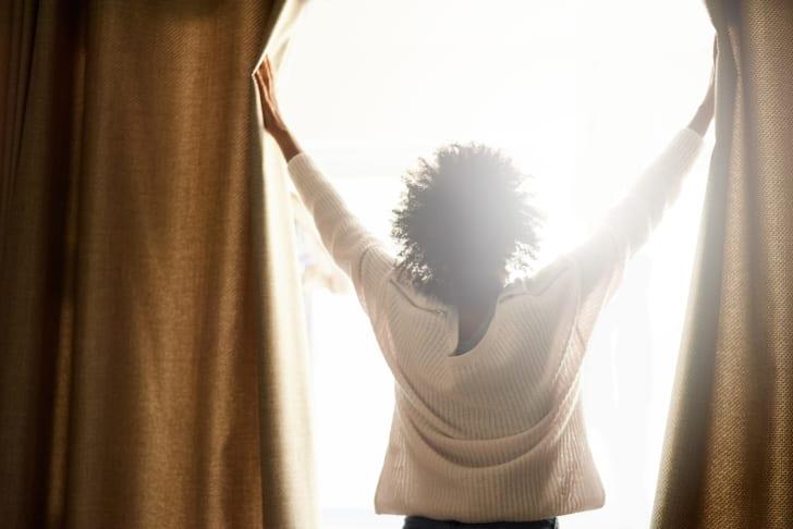 A woman in a white sweater with her back turned to us is opening heavy curtains, letting the sunlight stream in.