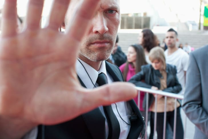 A bodyguard puts his hand up to the camera