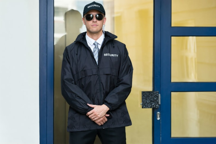 A security guard stands by a door