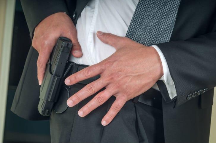 An armed bodyguard pulls a gun out of a holster