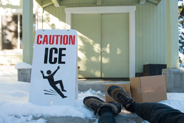 ice caution sign next to person who slipped on ice