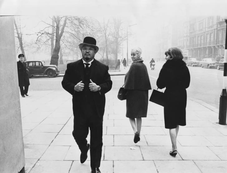 Professional wrestler and actor Toshiyuki 'Harold' Sakata wearing a suit and bowler hat, walking down a street in London, March 10th 1965.