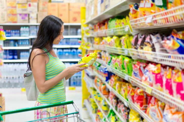 A shopper examines a bag of potato chips