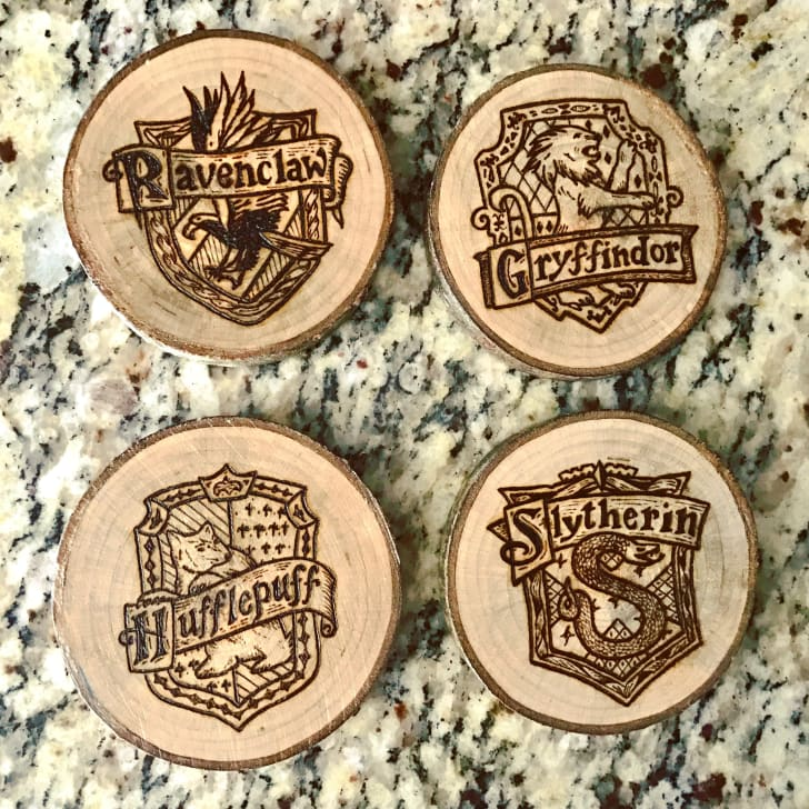 Set of wood burned coasters featuring the crest of each Harry Potter house