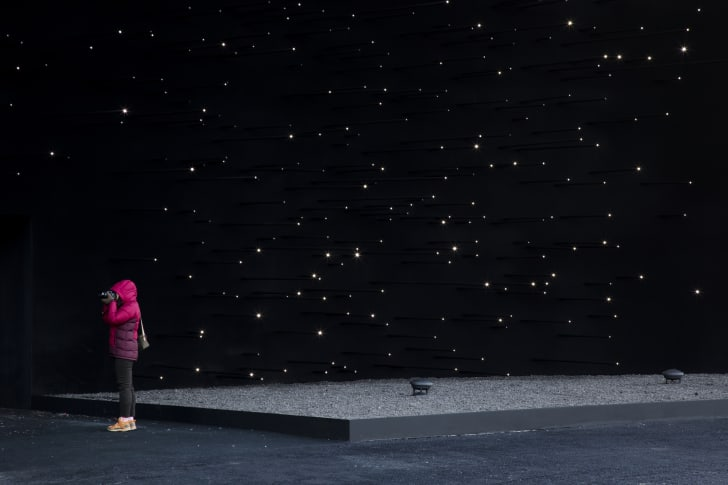 Child next to wall painted to look like the night sky.