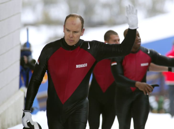 Monaco's bobsleigh pilot prince Albert Grimaldi and his teammates wave to the public after their sled tipped over during the Salt Lake 2002 Olympic Winter Games.