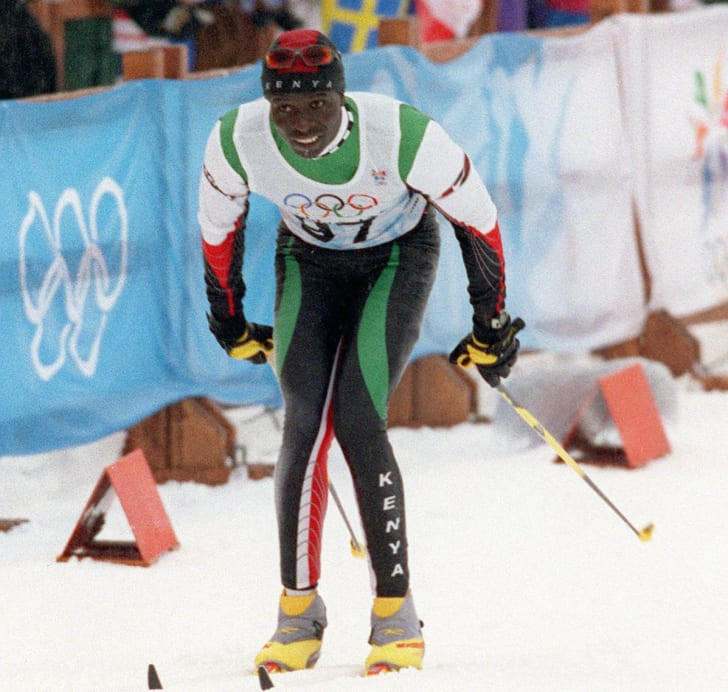 A crowd of spectators cheer as Kenyan Philip Boit finishes last during the men's 10km cross country event at the 1998 Nagano Winter Olympics