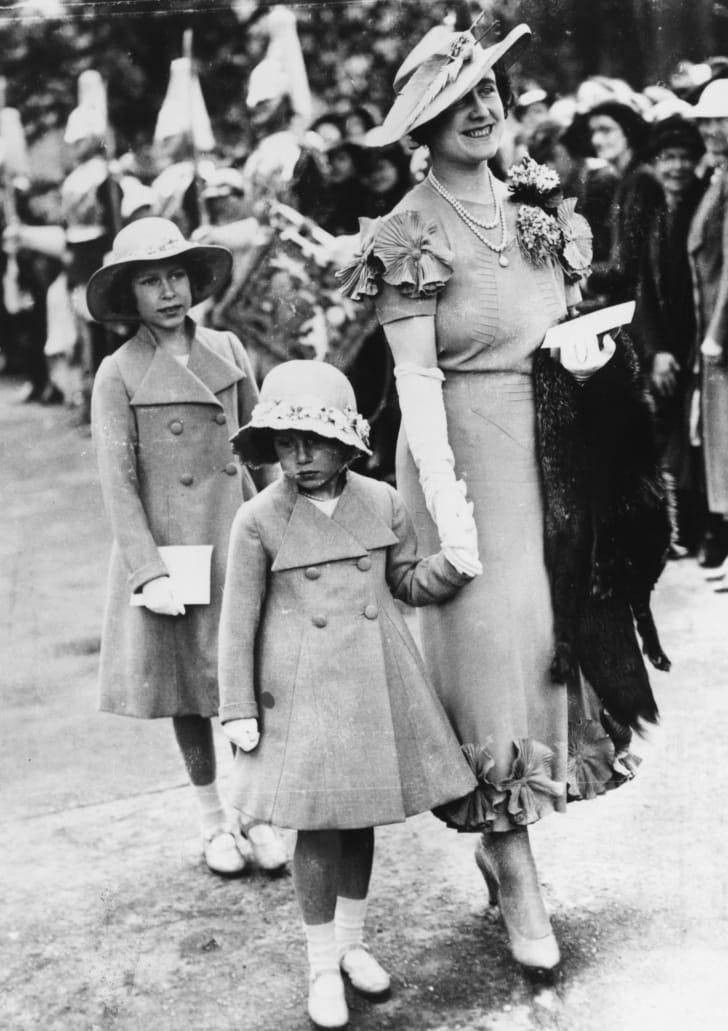 Queen consort Elizabeth holds Princess Margaret's hand as Princess Elizabeth follows, in 1936.