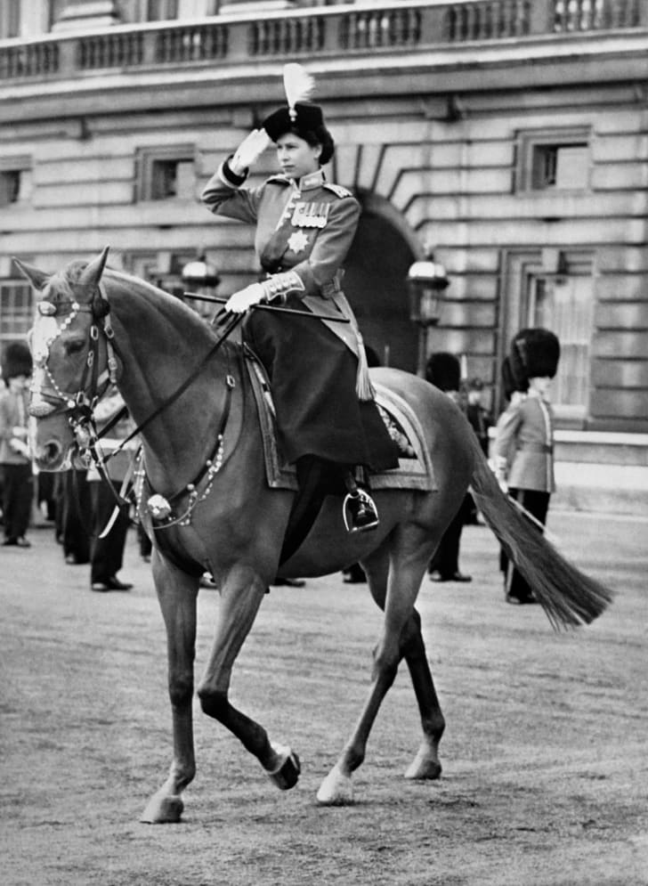Britain's Queen Elizabeth II rides a horse side saddle and salutes during a Trooping of the Colour ceremony in London in 1952.
