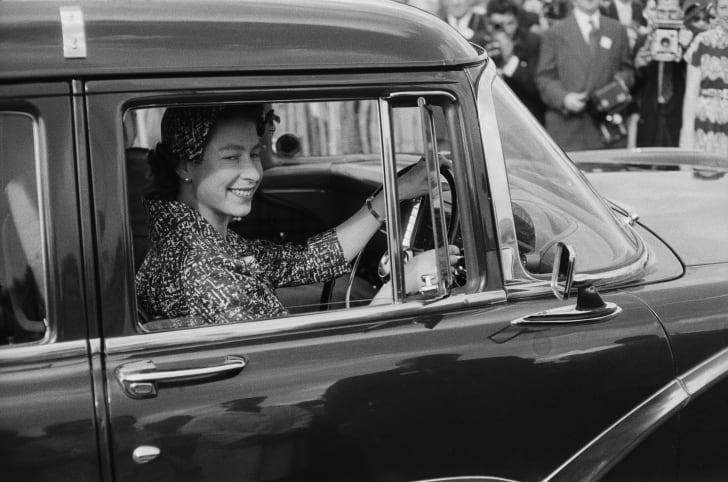 Queen Elizabeth II drives a car in 1958.