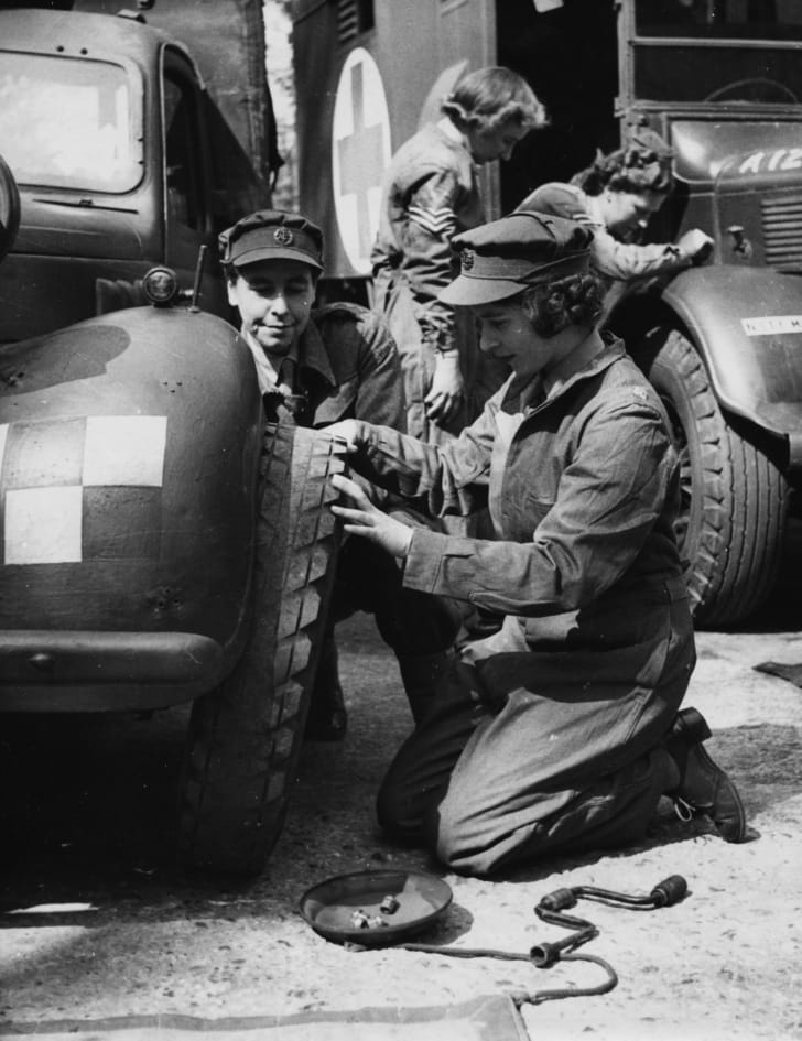 Princess Elizabeth changing the tire of a vehicle as she trains at as ATS Officer during World War II in April 1945.