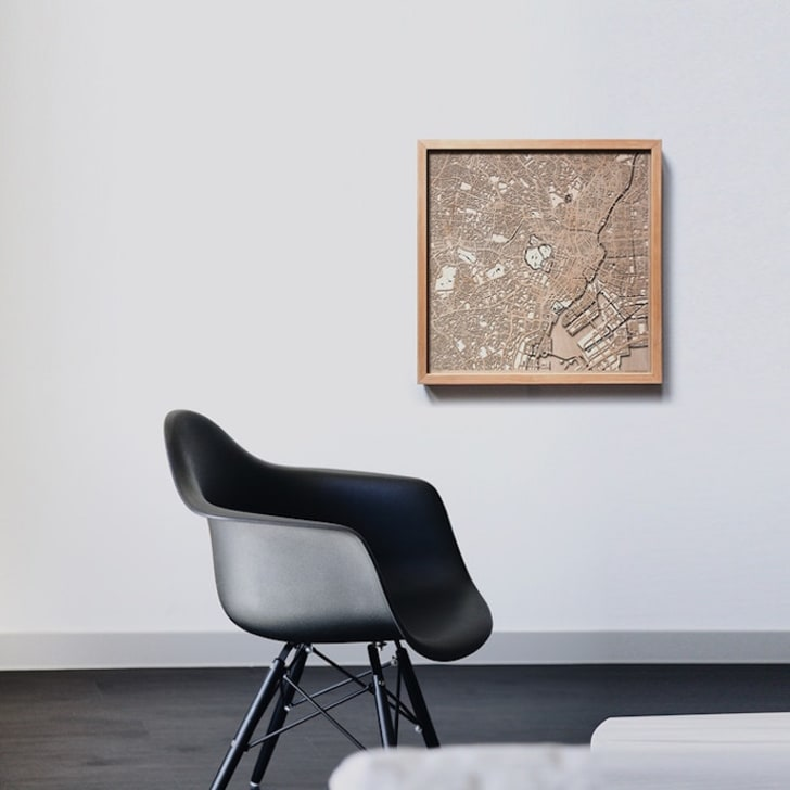 Wooden map on wall with chair.