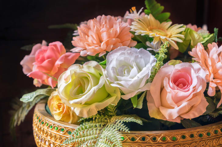 A basket full of pastel-colored fake roses and daises