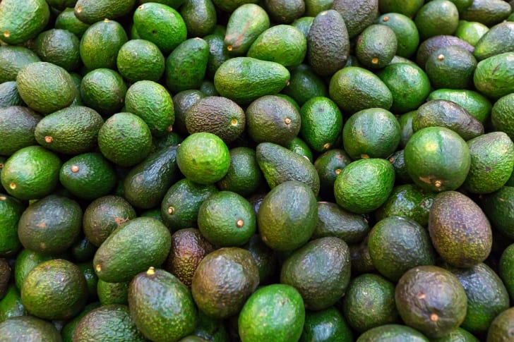 A pile of avocados in various stages of ripeness