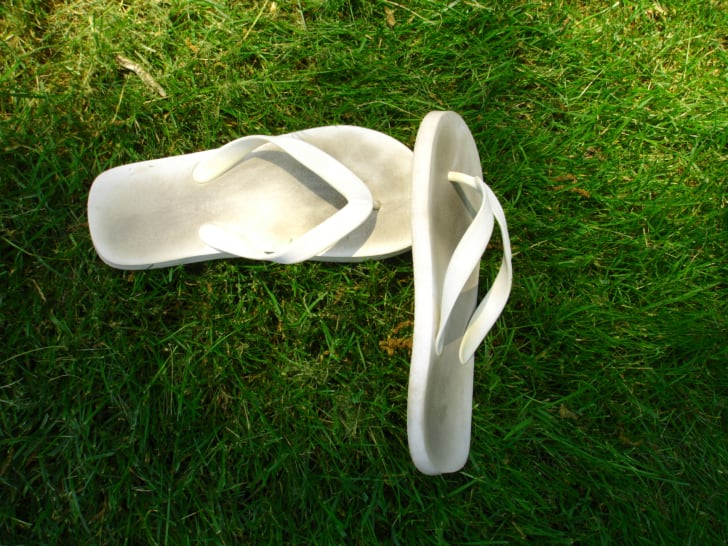 A pair of really dirty white flip-flops sitting on top of very green grass