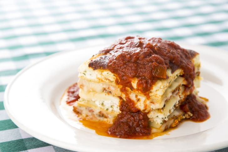 Lasagna with meat sauce sitting on a white plate on top of a green checkered tablecloth