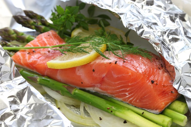 Raw salmon on top of asparagus spears and garnished with dill and lemon, all in a bed of aluminum foil.