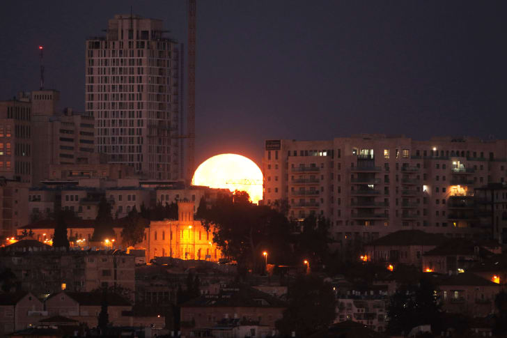The moon sets behind the city of Jerusalem early on January 31, 2018.