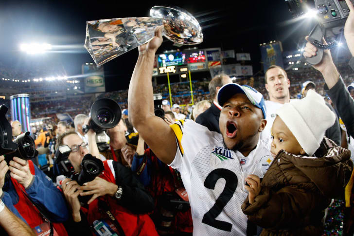 Mewelde Moore #21 of the Pittsburgh Steelers celebrates holds up the Vince Lombardi trophy as he celebrates with his daughter Jalyn Chantelle after their 27-23 win against the Arizona Cardinals during Super Bowl XLIII on February 1, 2009