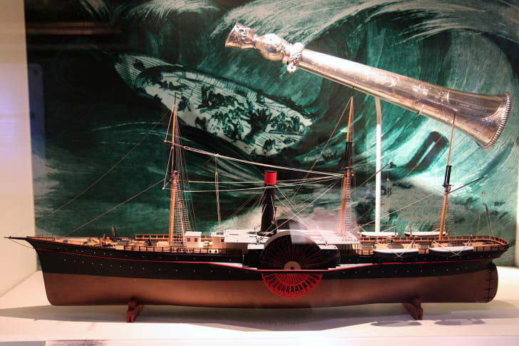 A model of the S.S. Central America sits in front of an illustration of a giant wave