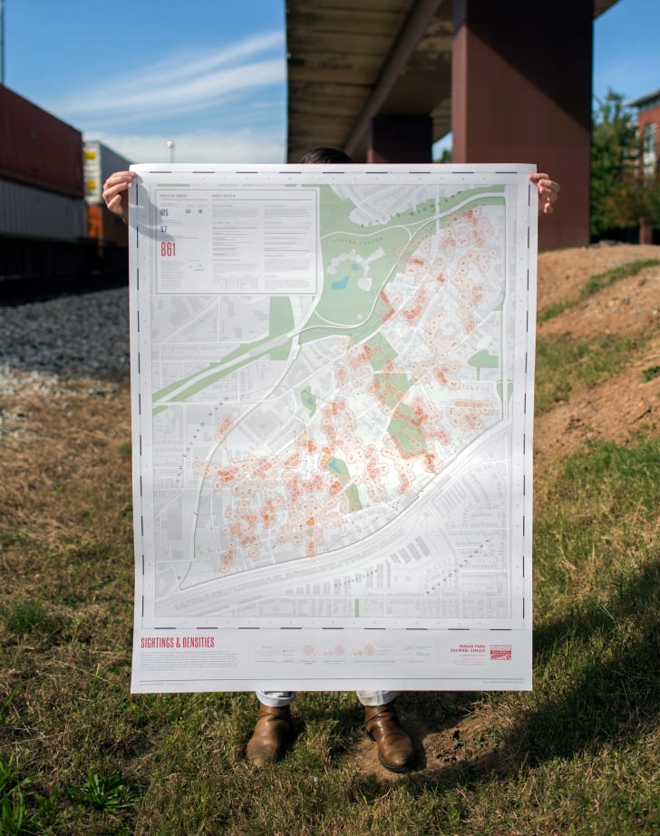 A person holds up an oversized map.