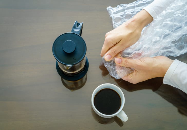 Woman popping Bubble Wrap on a table with coffee nearby.