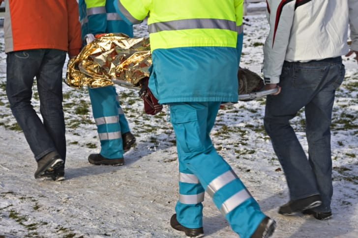 Emergency responders carrying a stretcher in the snow.