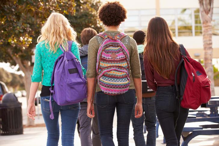 Three women wearing backpacks.
