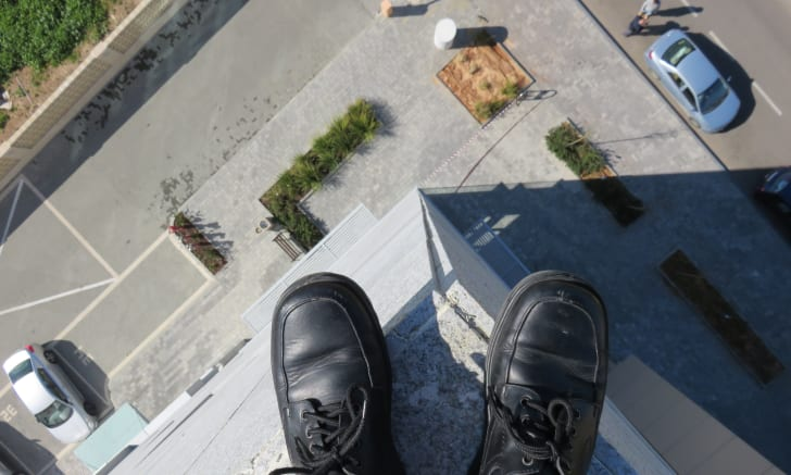 Feet on the edge of a building.