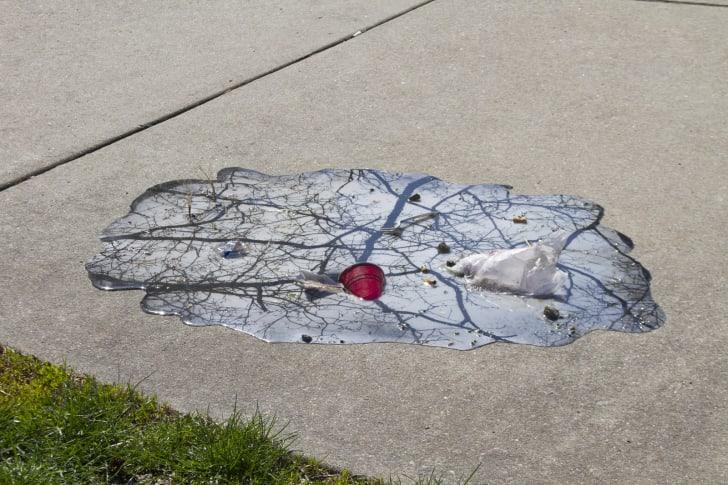 Puddle art on sidewalk.