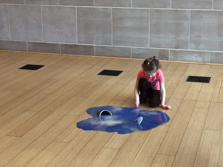 Child looking at puddle art.
