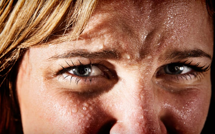 Close-up of perspiring, tense, frowning young blonde woman